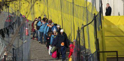 Refugiados caminan a lo largo de una valla instalada en la frontera con Eslovenia, en Spielfeld, Austria.