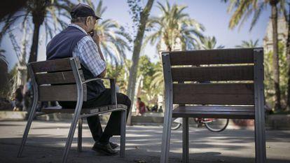 Un señor mayor descansa en un banco en la calle, en Barcelona.
