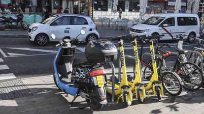Una motocicleta y tres patinetes de alquiler por minuto aparcados en la acera. Por la calzada, un coche de una de las empresas de vehículos compartidos.
