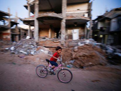 Un niño pasa en bicicleta ante una casa destruida por los bombardeos, el domingo en Gaza.