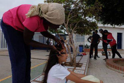 Una mujer subsahariana hace trenzas en el pelo a una niña melillense en la puerta del CETI de Melilla este miércoles.