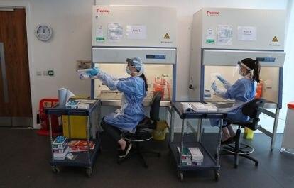 Trabajadores en un laboratorio de Glasgow realizan la fase final del test de coronavirus.