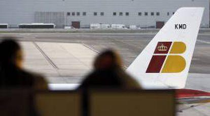 Dos personas ante un avión de Iberia, en el aeropuerto Adolfo Suárez - Barajas. EFE/Archivo