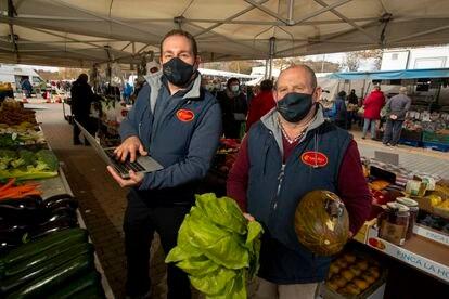 Carlos Gómez y su padre, Juan Gómez, en su puesto de  venta ambulante de fruta en Coslada.