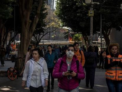Una mujer camina con un cubre bocas en Ciudad de México. En vídeo, declaraciones del subsecretario de Salud.