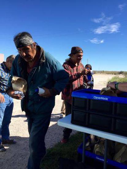 Louis y otro sioux cogen comida gratis de la organización de cristianos.