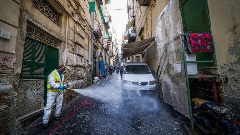 Un trabajador desinfecta una calle del Barrio Español en Nápoles, este miércoles.