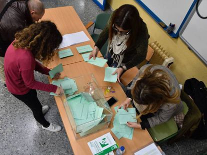 Varias personas recogen papeletas en un colegio electoral de El Ejido (Almería), este domingo.