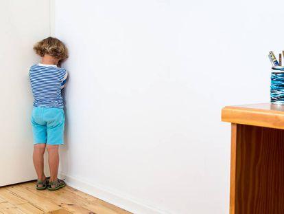 Un niño está castigado contra la pared.