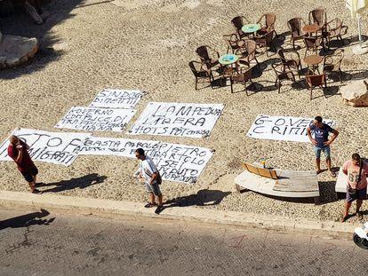 Residentes de Lampedusa ponen pancartas en señal de protesta contra el Gobierno central ante la falta de gestión de la inmigración en la isla, este lunes.