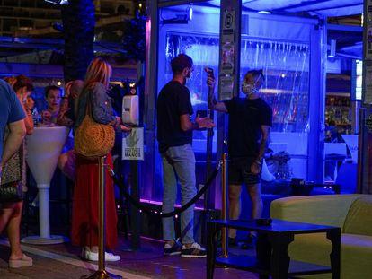 Un empleado toma la temperatura a un joven para entrar en un pub en el puerto deportivo de Marbella, este domingo.