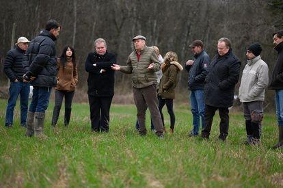 Jean-Baptiste Moreau (de negro, con los brazos cruzados) durante una conversación con agricultores sobre el glifosato.