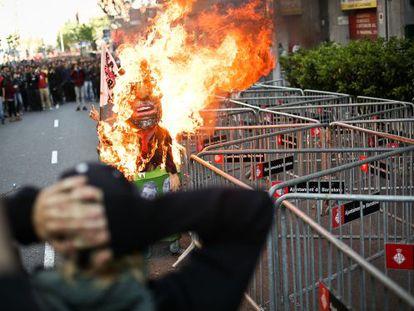 Un muñeco imitación de Mariano Rajoy arde ante la sede del PP.