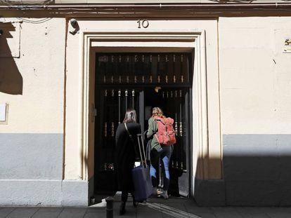 Dos personas entran a un piso de alquiler turístico, en la calle de Encomienda 10, en Madrid.