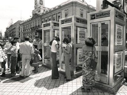 Usuarios de cabinas telefónicas esperan en la Puerta del Sol de Madrid en 1985