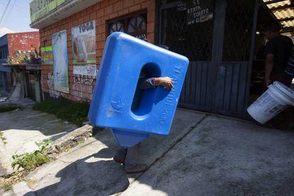 Un trabajador carga un sistema de captación de agua de lluvia de la empresa Isla Urbana.