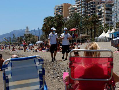 Una pareja de vigilantes recorren la playa de La Malagueta (Málaga).