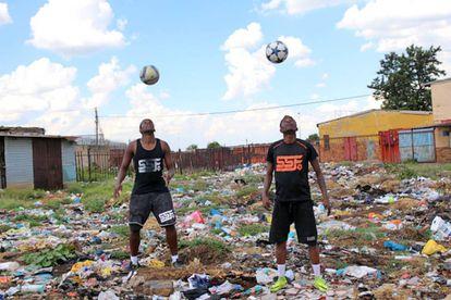 Dos jóvenes hacen malabares durante una actuación del colectivo de artistas Street Arts Government, en Sharpeville.