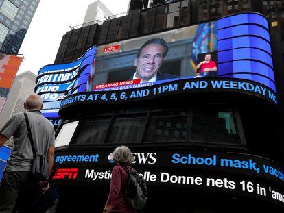 La gente pasa caminando mientras el gobernador de Nueva York, Andrew Cuomo, transmite en vivo su discurso de despedida en una pantalla en Times Square, Nueva York, el 23 de agosto de 2021.