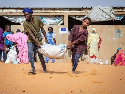 Niños cargan un saco de arroz que acaban de recibir en el campamento de refugiados de Mbera, Mauritania, el pasado 1 de junio.