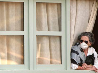 Una mujer mira por la ventana en su habitación del hotel H10 Costa Adeje Palace, en Tenerife, el 26 de febrero.