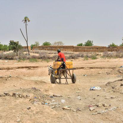 """<b>Un carro cargado con garrafas de agua atraviesa el cauce seco de un río a la entrada de Boully.</B> En la ciudad de Boully, a pocos kilómetros del imponente río Senegal, que hace de frontera natural entre el país mauritano y el senegalés, se está viviendo un """"tsunami"""". """"Esto es un tsunami [de personas que emigran]. Muchísima gente se va porque aquí ya no puede ganarse la vida. Sobre todo los jóvenes, que creen que su futuro aquí no existe. Hay que hacer algo, porque sin jóvenes un pueblo no crece"""". Quien habla es uno de los ancianos de esta ciudad de 10.000 almas. Nos explica que la mayoría huyen hacia destinos cercanos pero que algunos han emprendido el viaje hacia Europa. """"No sé si lo han conseguido o no, pero aquí no han vuelto""""."""