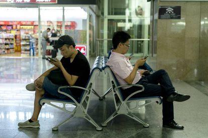 Ciudadanos de la China usan sus móviles mientras esperan al tren en la estación de Tianjin.