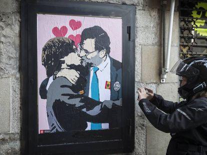 Una intervencion artistica de TVBoy en una calle contigua al Palau de la Generalitat, muestra como Rajoy y Puigdemont se dan un beso en la boca.