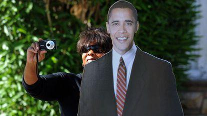 Una mujer se fotografía junto a un póster gigante de Obama.