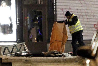 Un policía tapa el cadáver del fallecido tras un doble ataque en una zona comercial de Estocolmo, en el que también han resultado heridas otras dos personas.