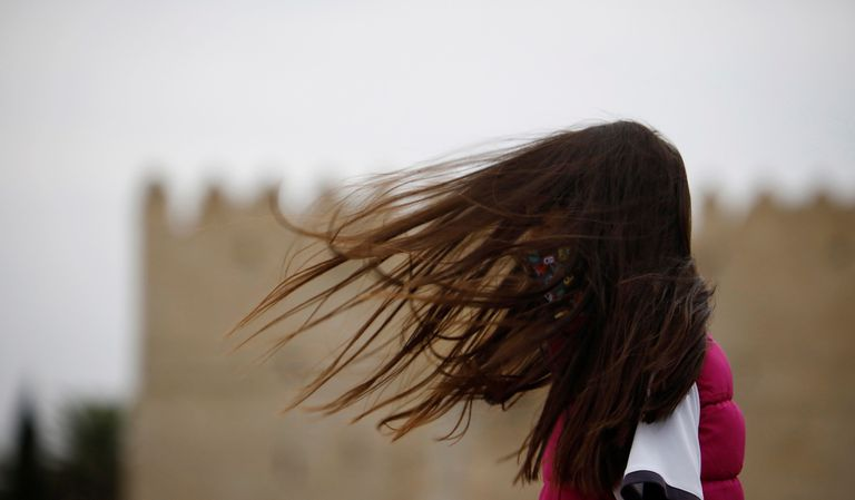 Una joven camina este martes en Córdoba, en una jornada muy ventosa.