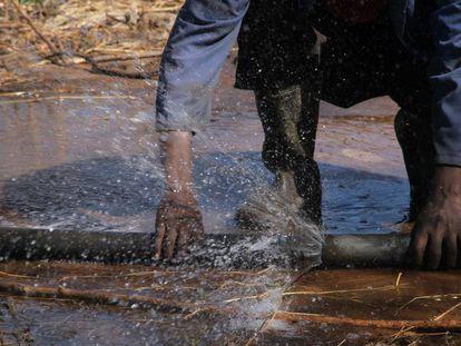 Un agricultor junta dos tuberías para el regadío de una parcela en Zimbabue.