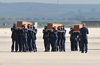 Varios militares llevan a hombros los féretros con los restos mortales de los periodistas David Beriáin y Roberto Fraile y del conservacionista irlandés Rory Young, asesinados el lunes en Burkina Faso.