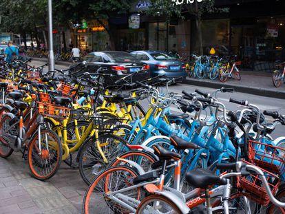 Decenas de bicicletas compartidas inundan las aceras de esta calle de Pekín.