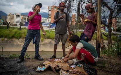 Un grupo de niños busca comida entre bolsas de basura en Caracas el pasado noviembre.