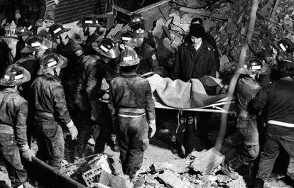 Los bomberos trasladan a uno de los cadáveres rescatados del sótano del restaurante El Descanso, en abril de 1985.