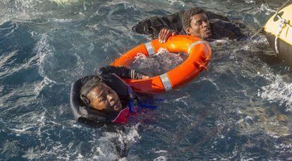 Dos inmigrantes que viajaban en las balsas hinchables son sacados del agua, a la que se lanzaron antes de ser rescatados.