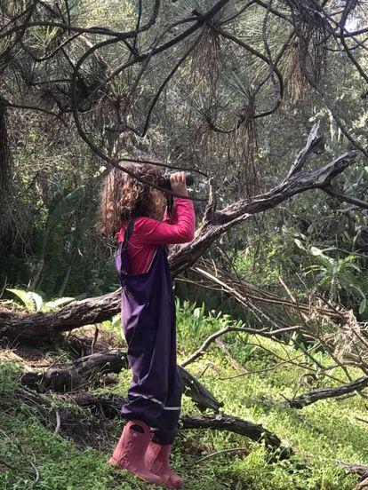 Una alumna de la escuela en la naturaleza Bosqueko observa varias aves desde el bosque con sus prismáticos.