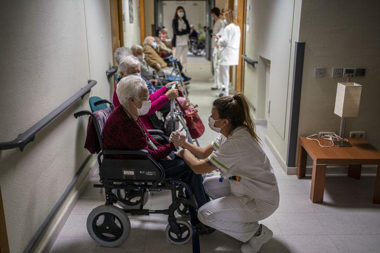 Ancianos de la residencia de mayores Domusvi de Leganés, en Madrid, esperan en un pasillo para recibir la vacuna.
