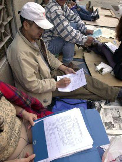 Inmigrantes rellenan sus papeles para entregarlos en una oficina de la Delegación del Gobierno de Madrid.