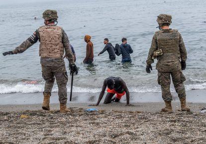 Un hombre arrodillado en una playa de Ceuta mientras el Ejército acordona la zona, el pasado martes.