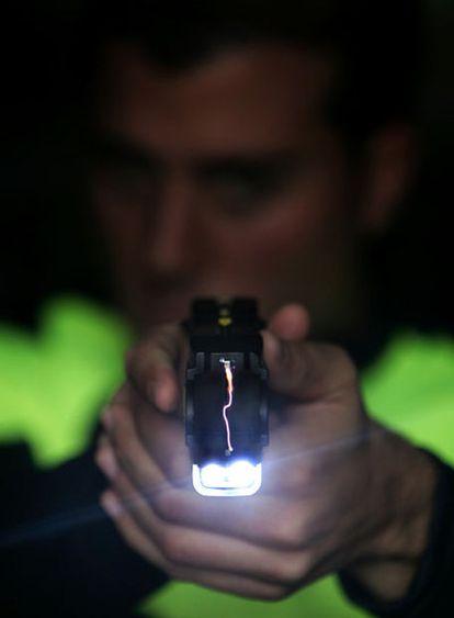 Un agente de la Policía Local de Moraleja de Enmedio (Madrid) empuña una pistola Taser.