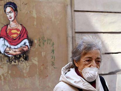 Una mujer con una mascarilla camina por el distrito judío en el centro de Roma el 24 de marzo de 2020.