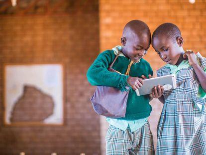 Dos alumnos de primaria de un colegio de Kenia con las tabletas que utilizan gracias un proyecto español.