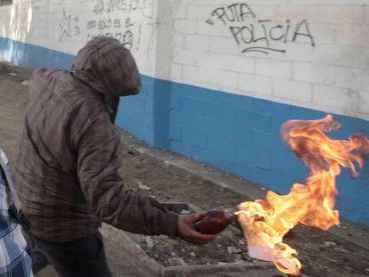 Un joven lanza un cóctel molotov.