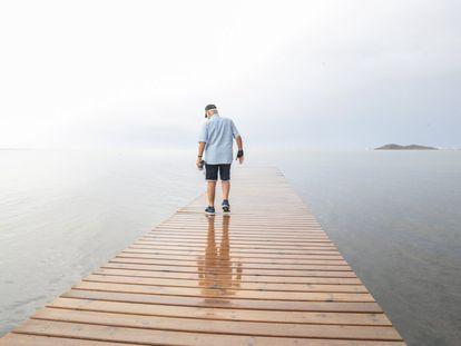 Ángel Pérez, vecino de Los Urrutias, observa el agua sucia del mar Menor desde un embarcadero próximo a su casa.