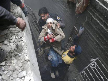 Miembros de la Defensa Civil Siria rescatan a una mujer tras un bombardeo en Duma.