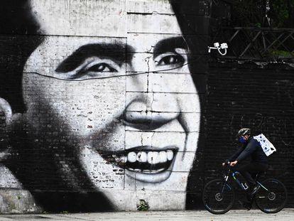 Un hombre con barbijo pasa con su bicicleta delante de un mural con el rostro de Carlos Gardel, en Buenos Aires, el 4 de mayo de 2020.