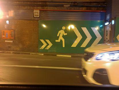 Un cartel enseña la dirección hacia la salida de emergencia en los túneles de María de Molina.