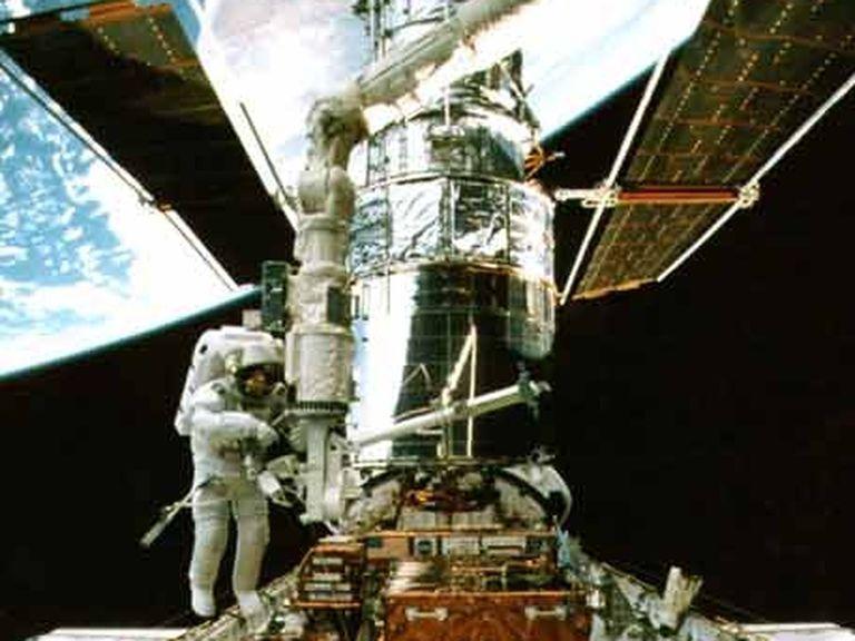 Un astronauta trabaja en el <i>Hubble</i>, sobre el transbordador, en 1997.» class=»block width_full»><figcaption class=